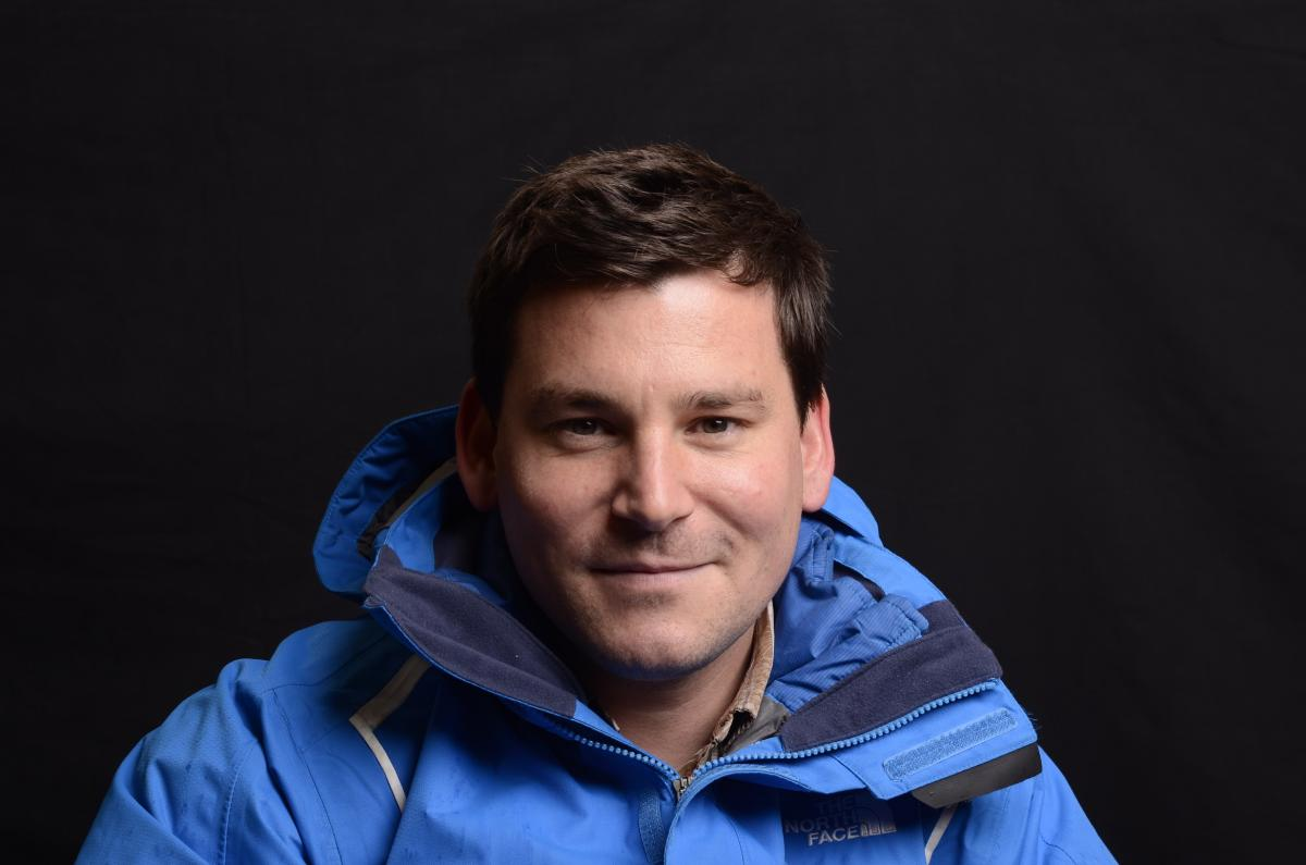 A photograph of Simon White who is smiling and wearing a blue jacket.